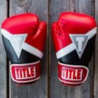 Photo of two MMA/boxing gloves on a wooden floor