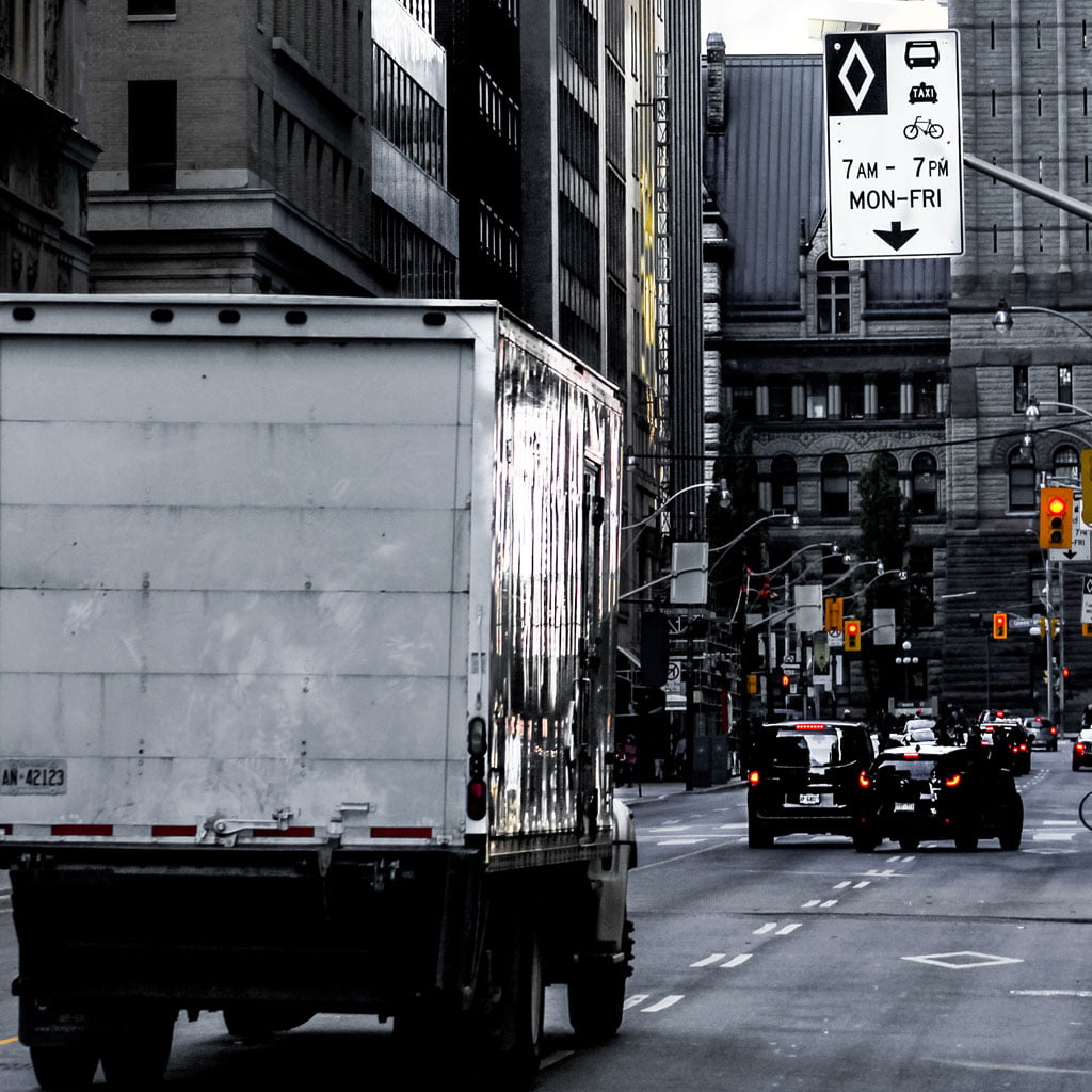 Photo of a delivery truck driving on a city street.