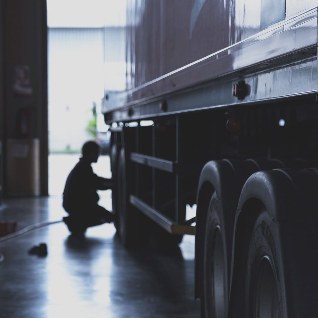 Heavily shadowed photo of a male performing maintenance on a semi-truck trailer