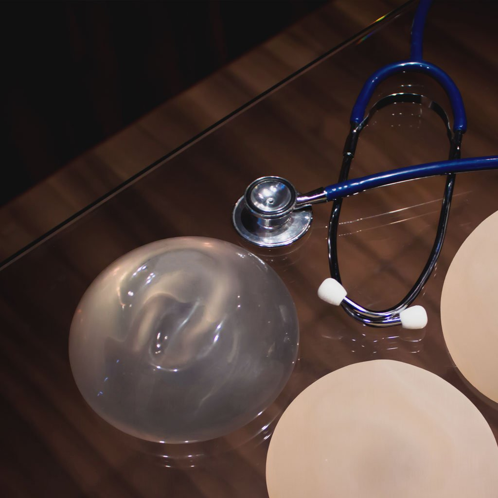 Close-up photo of a table featuring two silicone implants and a stethoscope