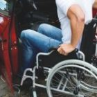 Photo of a blue-collar male trying to enter a car from a wheelchair